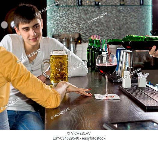 Attractive young man chatting to his girlfriend over a beer at the bar smiling as he listens to her talking, view from behind the woman with only her arm...