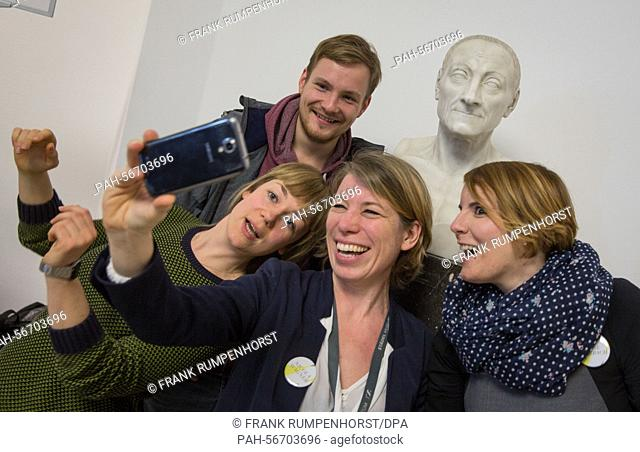 Employees of the museum take a selfie in front of a bust of the founder Johann Friedrich Städel (1728-1816) during the anniversary celebrations in Frankfurt a