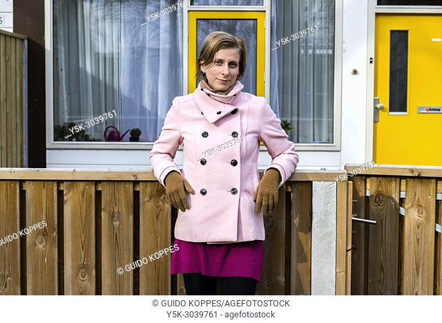 Tilburg, Netherlands. Portrait of a young, caucasian woman, standing proudly in front of her newly aquired apartment at the north side of town