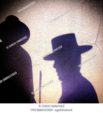 The shadow of two flutists wearing hats is cast in a wall in Prado del Rey, Sierra de Cadiz, Andalusia, Spain