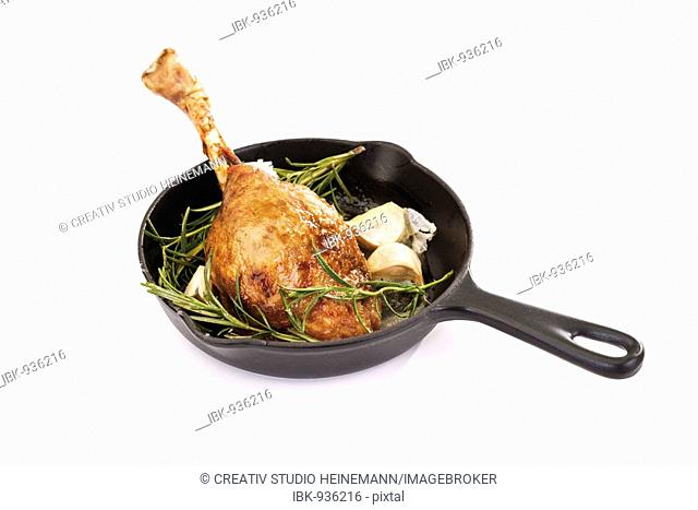 Leg of roast goose in a cast-iron pan