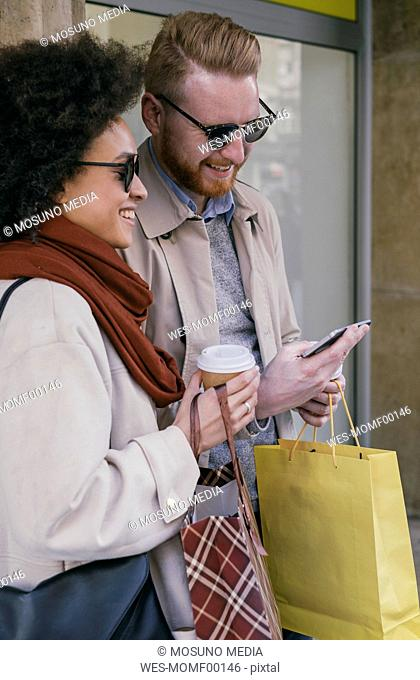 Happy couple in the city with cell phone and shopping bags