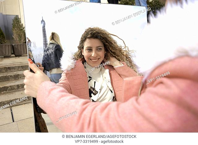 woman looking in mirror, outdoors in city, near tourist sight Eiffel Tower, at Espl. du Trocadéro, in Paris, France