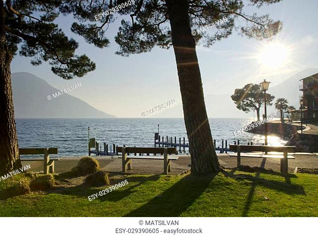 Lakefront with trees and benches in backlight with sunbeam and mountain with blue sky