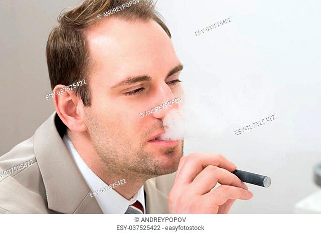 Portrait Of Young Businessman Smoking Electronic Cigarette