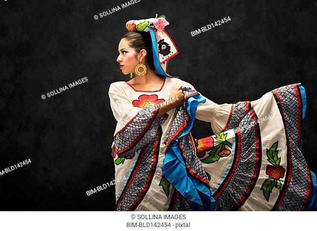 Hispanic teenage girl dancing in Sinaloa Folkloric dress