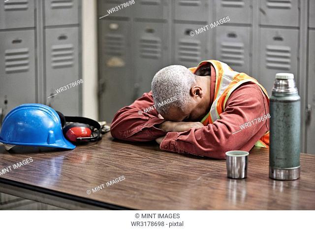 Black man factory worker taking a break from work in a factory locker room