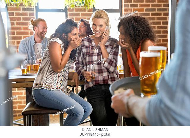 Group Of Female Friends Making Phone Call In Bar Together