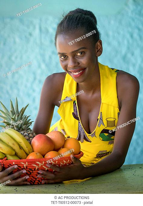 Smiling young woman holding fruit bowl