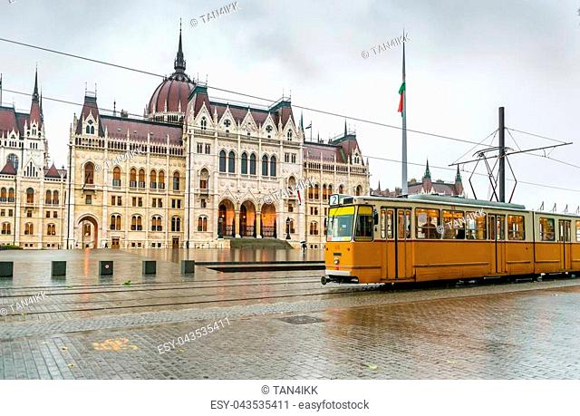 yellow Budapest tram in front of Hungarian National Parliament