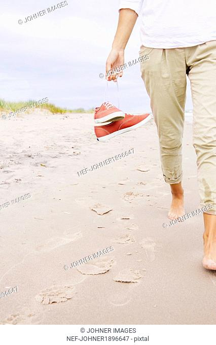 Woman on beach carrying shoes, close-up