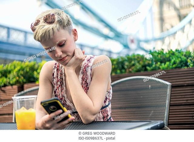 Young woman sitting outdoors, plastic drinking glass in front of her, looking at smartphone