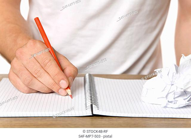 Man writing with color pencil in notebook