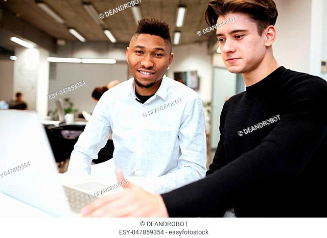 Photo of two students sitting in library and using laptop computer. African guy looking at camera. Caucasian man look at laptop