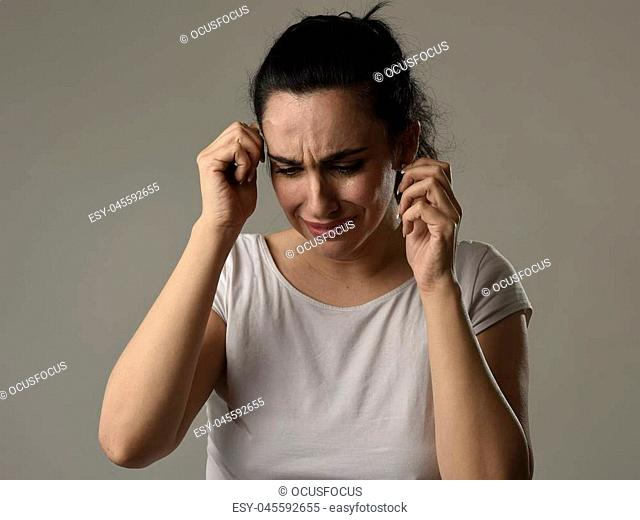 beautiful face of sad woman crying desperate and depressed with tears on her eyes suffering pain and depression isolated on grey background in sadness facial...