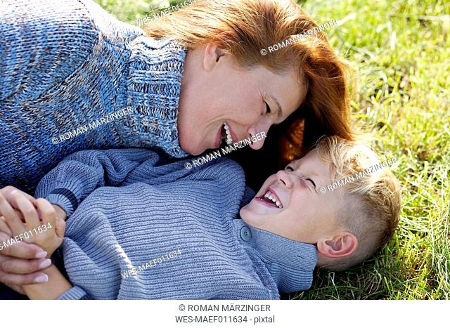 Carefree mother and son lying in meadow