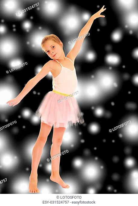 Charming little girl ballerina in a pink translucent dress.On a black background with white Christmas snowflakes