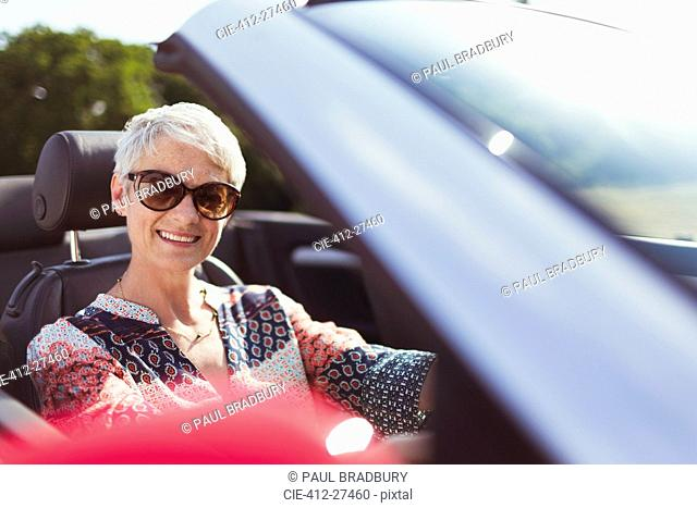 Portrait smiling senior woman in sunglasses driving convertible