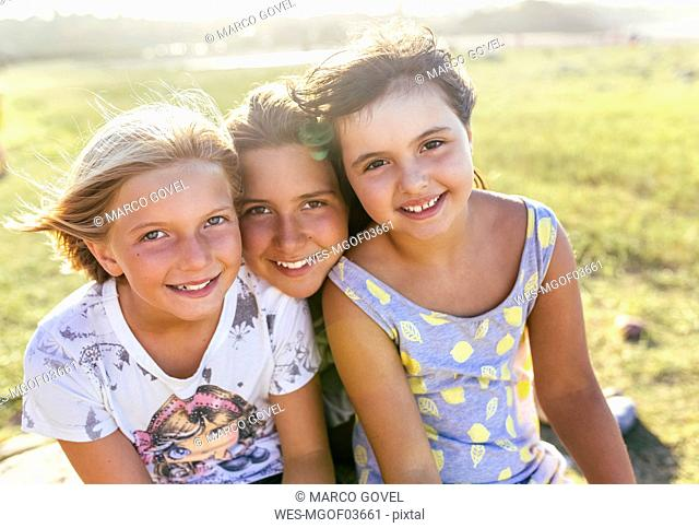 Group picture of three girls head to head in summer