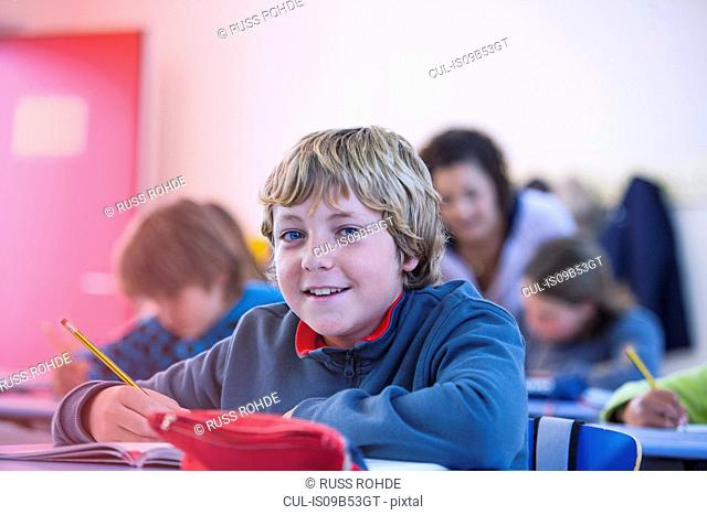 Portrait of boy in classroom, sitting at desk, smiling