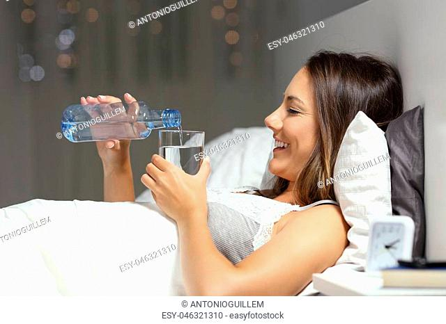 Side view portrait of a happy woman throwing water in a glass from a bottle in the bed in the night at home