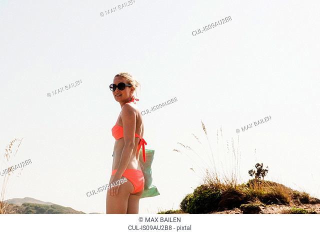 Portrait of woman wearing bikini in dunes, Menorca, Spain