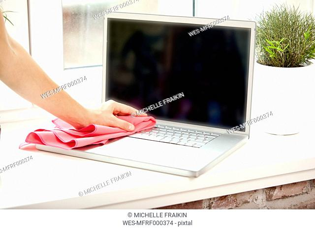 Woman cleansing laptop with duster