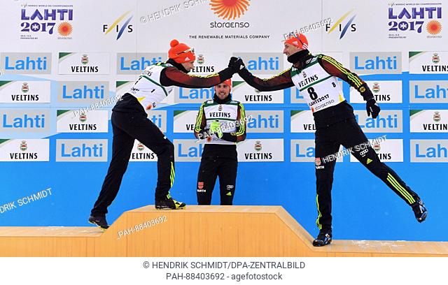 Johannes Rydzek (c, 1st Place), Eric Frenzel (l, 2nd Place) and Bjoern Kircheisen (3rd Place), all from Germany, celebrate after the single combination event...