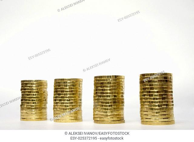 Four stacks of coins on a light background