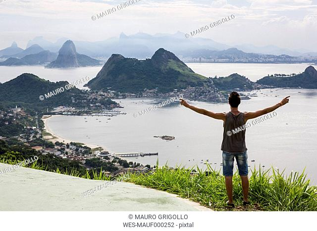 Brazil, Rio de Janeiro, tourist standing at view point, raising arms