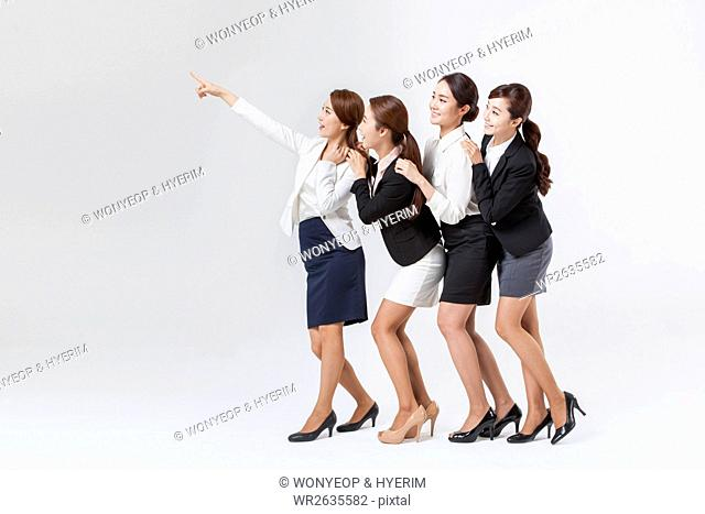 Side view of four young smiling businesswomen standing in line looking up