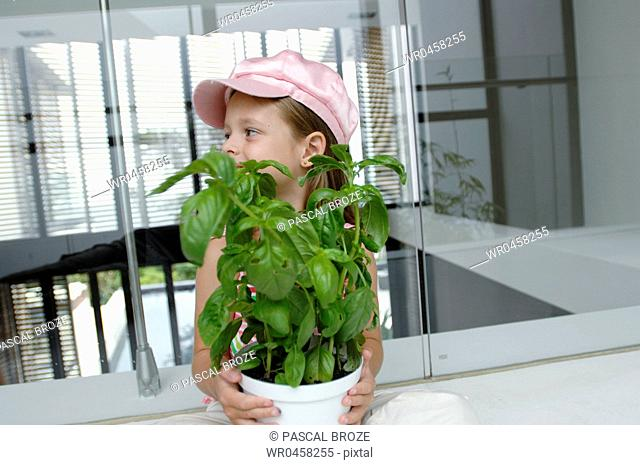 Close-up of a girl holding a potted plant