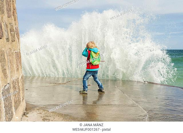 Germany, Mecklenburg-Western Pomerania, Ruegen, Sassnitz, Excited boy on pier with splashing water