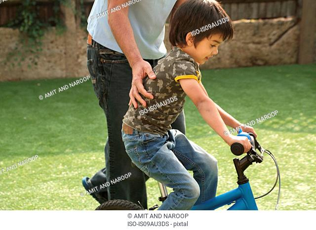 Side view of father supporting boy learning to ride bicycle