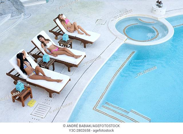 Three young attractive hispanic women using loungers for tanning next to swimming pool