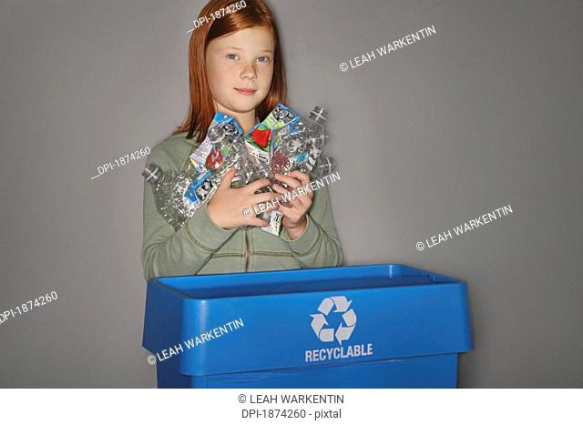 edmonton, alberta, canada, a girl putting plastic bottles and juice boxes into a blue recycle box