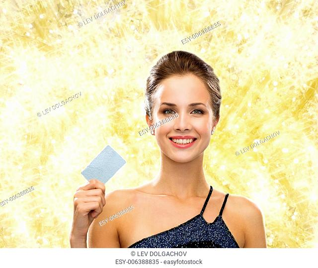 shopping, wealth, christmas, holidays and people concept - smiling woman in evening dress holding credit card over yellow lights background