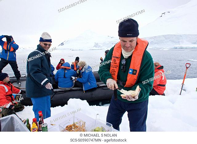 Guests from the Lindblad Expedition ship National Geographic Explorer enjoy a hot asado sandwich prepared by staff at BBQ on an ice floe near Adelaide Island