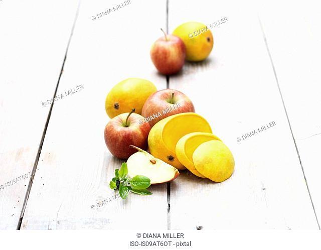 Still life of apple and mango slices on whitewashed wooden table