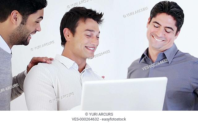 Young businessman showing something funny on his laptop to his two males co-workers