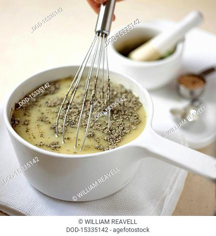 Using whisk to mix in rosemary in saucepan of soup