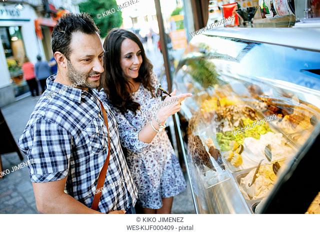Couple choosing ice cream in an ice cream shop showcase
