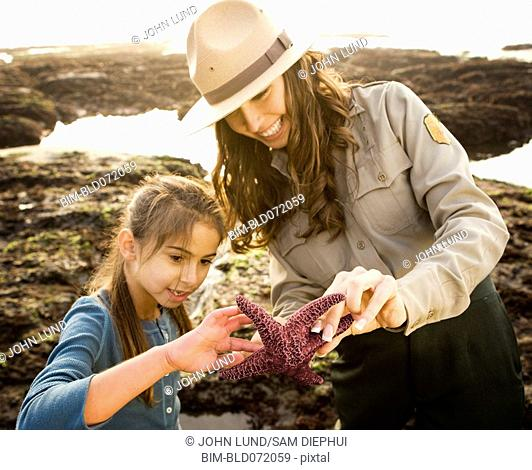 Mixed Race female park ranger and girl looking at starfish