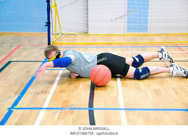 Team Player blocking ball from going into goal during a Goalball game, a threeaside game developed for the visually impaired and played on a volleyball court