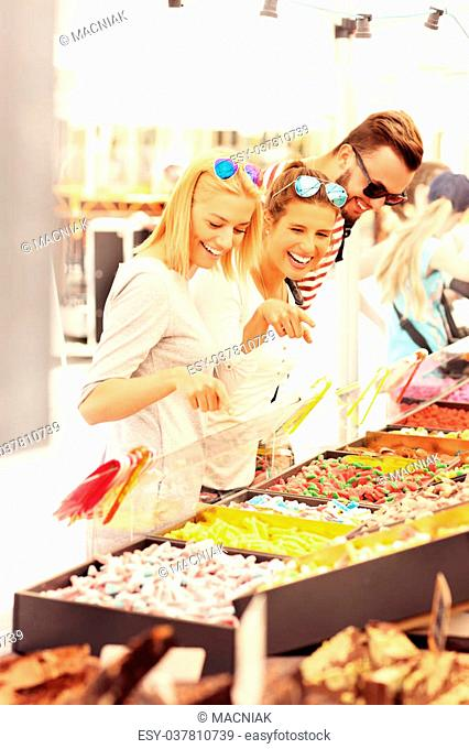 A picture of a group of friends buying jelly sweets on market