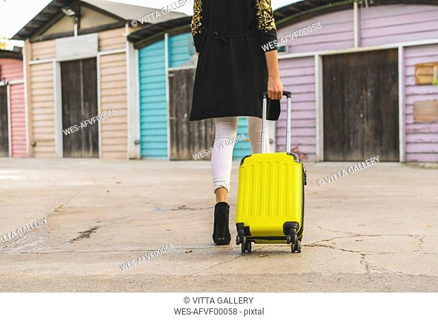 Back view of walking woman with yellow trolley bag, partial view