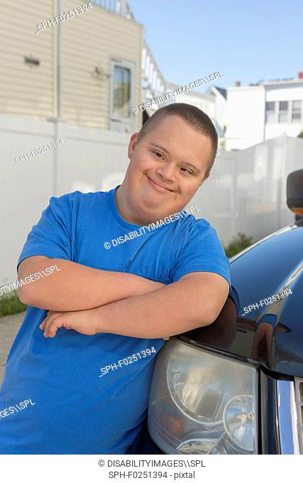 Teen with Down Syndrome leaning against a car