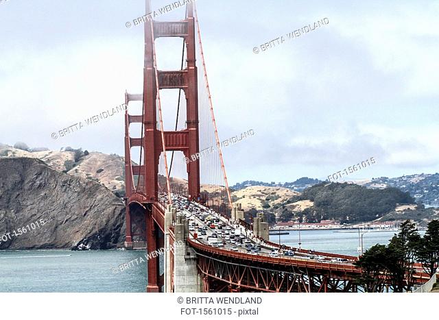 View of Golden Gate Bridge over bay of water against mountain during foggy weather