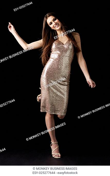 Young dark haired woman in evening dress dancing, vertical