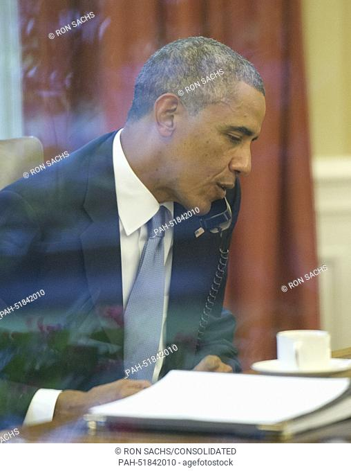 United States President Barack Obama is photographed through an Oval Office window as he speaks on the phone with King Abdallah Abd al Aziz of the Kingdom of...
